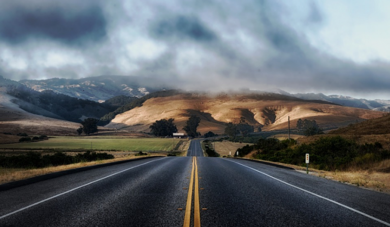 image of countryside with a long road disappearing into the distance.
